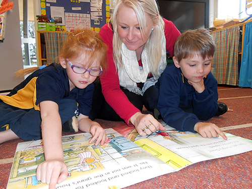 Teacher reading big book with two children.